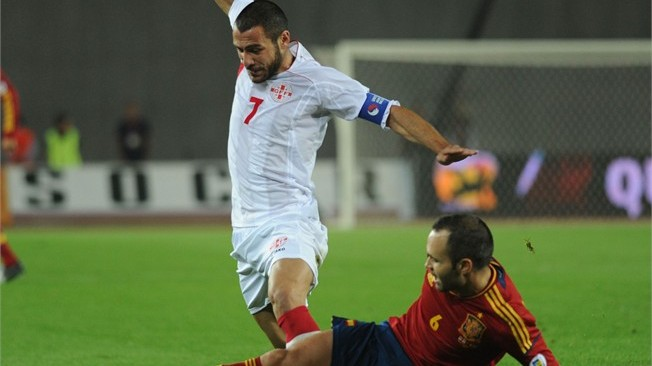 Georgia's captain Jaba Kankava evades Spain's Andres Iniesta in Tbilisi in September 2012