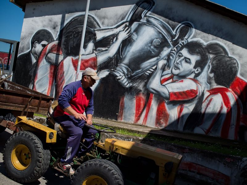 A maintenance worker drives past a mural at the Red Star Belgrade Marakana stadium on April 27, 2016, 25 years after the Red Star Belgrade European Cup final, an apotheosis of Yugoslav football before the country's bloody collapse. When the crowd hailed Pancev's final goal, the football legend, Red Star technical director at the time Dzajic, opened his eyes to fall into the arms of coach Ljupko Petrovic. The club, where he remains the top scorer, is now only a shadow of what it once was. The same as Marakana which was proud of its capacity of 100,000 people. (ANDREJ ISAKOVIC/AFP/Getty Images)
