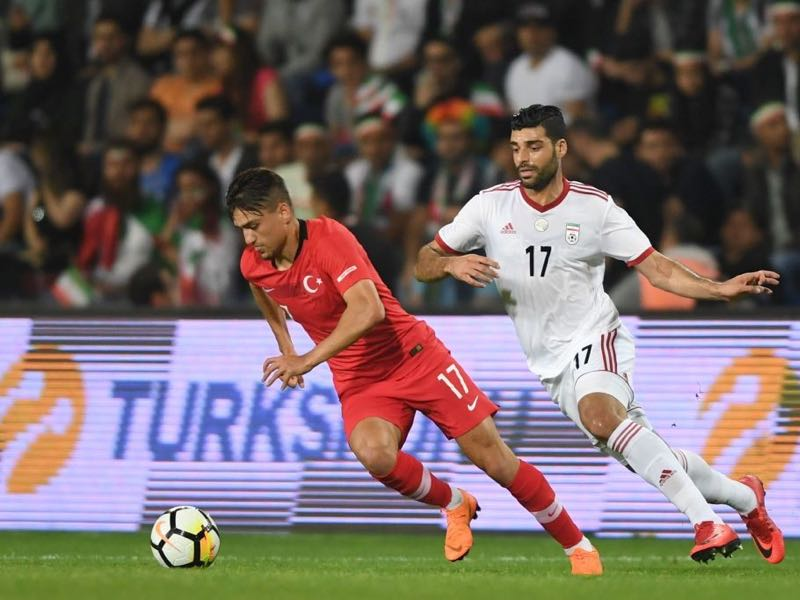 Turkey's Cengiz Ünder (L) vies for the ball with Iran's Mehdi Taremi (R) during the friendly football match between Turkey and Iran at Basaksehir Fatih Terim stadium in Istanbul on May 28, 2018. (Photo by OZAN KOSE / AFP)