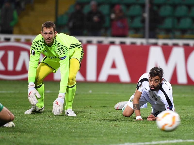 Vorskla FC goalkeeper Bohdan Shust (L) and Sporting Lisbon's Portuguese midfielder Bruno Fernandes eye the ball during their UEFA Europa League, Group E, football match Vorskla vs Sporting Lisbon at the Vorskla Stadium in Poltava on October 4, 2018. (Photo by SERGEI SUPINSKY / AFP)