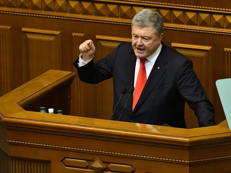 Ukrainian President Petro Poroshenko delivers his speech from Parliament tribune during an emergency session in Kiev on November 26, 2018, ahead of a parliamentary vote on the request of the Ukrainian President to impose martial law in the country. - Ukraine's parliament approved the introduction of martial law on November 26 in the border regions of the country for 30 days, after Moscow seized three of Kiev's ships in a confrontation at sea. (Photo by Genya SAVILOV / AFP)