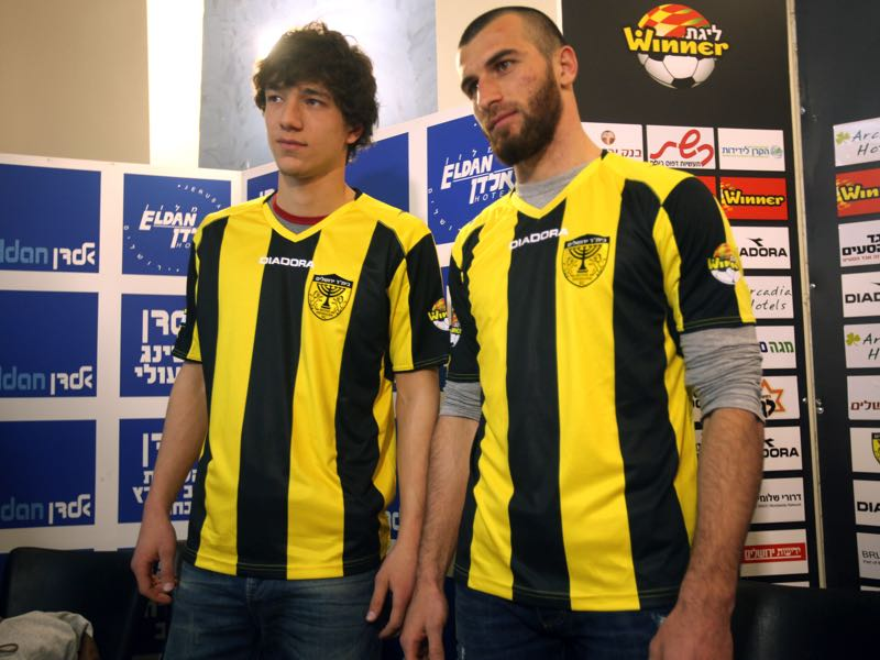 Chechen football players Dzhabrail Kadaev (L) and Zaur Sadaev, signed from Russian League club Terek Grozny, show off their new shirts during their introduction by the Beitar Jerusalem football club to the press in Jerusalem on January 30, 2013. Beitar Jerusalem, owned by Russian-Israeli Arkady Gaydamak, is in turmoil after some fans lashed out at the owner's plan to sign the two Muslim players, insisting the club would remain 'pure' and causing uproar during a weekend game. (AHMAD GHARABLI/AFP/Getty Images)