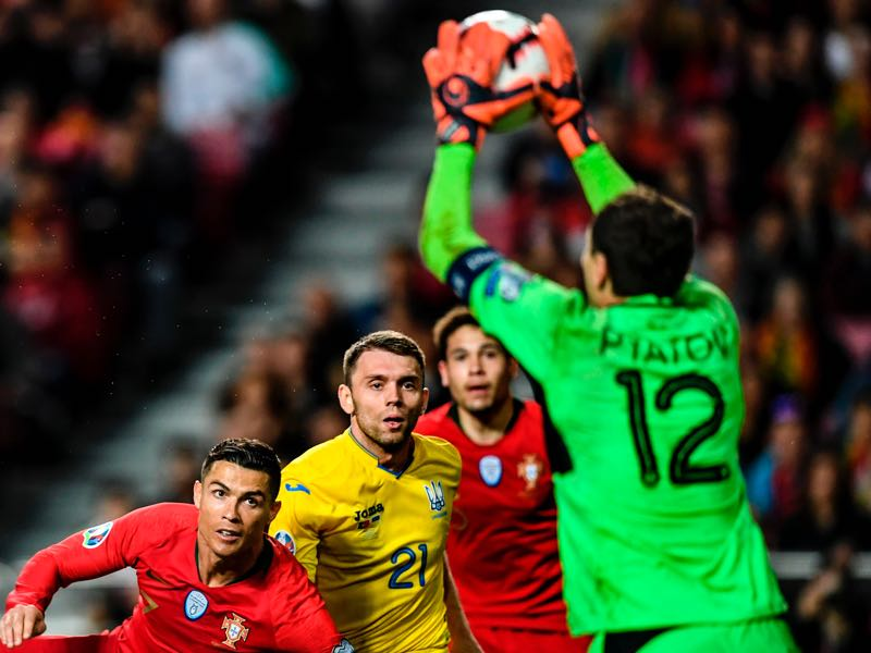 Portugal v Ukraine - Ukraine's goalkeeper Andriy Pyatov (R) stops a shot on goal by Portugal's forward Cristiano Ronaldo (L) during the Euro 2020 group B qualifying football match between Portugal and Ukraine at the Luz stadium in Lisbon on March 22, 2019. (Photo by PATRICIA DE MELO MOREIRA / AFP)