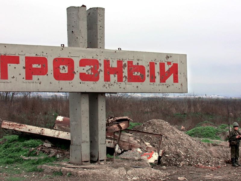 "A Russian soldier stands next to the ""Grozny"" board at the entrance of the city 29 March 2001. AFP PHOTO ALEXANDER NEMENOV (Photo credit should read ALEXANDER NEMENOV/AFP/Getty Images)"