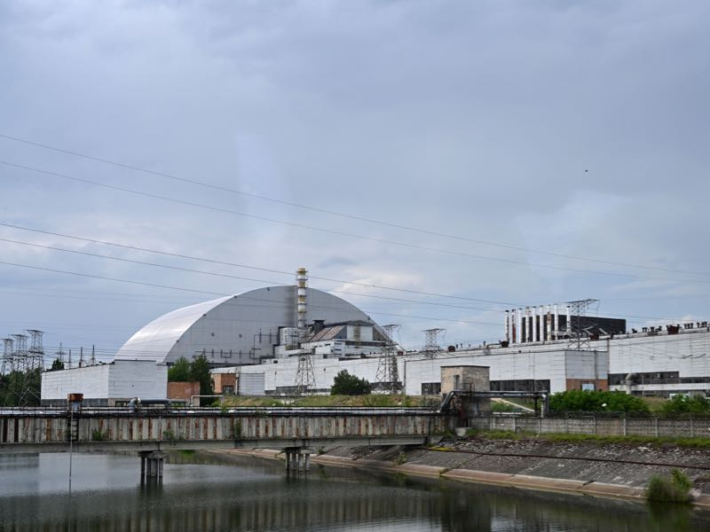 A picture taken on June 7, 2019, shows the Chernobyl nuclear power plant and the Chernobyl's New Safe Confinement covering the 4th block (reactor 4) of Chernobyl Nuclear power plant. - HBOs hugely popular television series Chernobyl has renewed interest around the world on Ukraines 1986 nuclear disaster with authorities reporting a 30% increase of tourist demands to visit the affected area and tourist operators forecasting that number of tourists visiting the site may double this year up to 150.000 persons. (Photo by Genya SAVILOV / AFP)